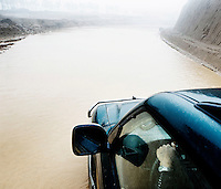 A car drives along a flooded road at a coal mining industrial site in Shanxi Province.
