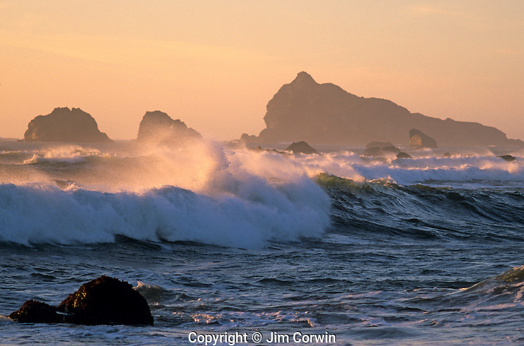 Northern California Crescent city ruff surf with waves breaking onto shoreline with rock formations at sunset Crescent City California USA