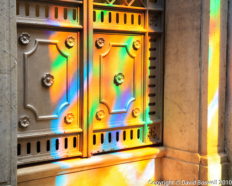 The sun shining through stained glass provides a kaleidescope of colors in the Cementario de la Recoleta in Buenos Aires.