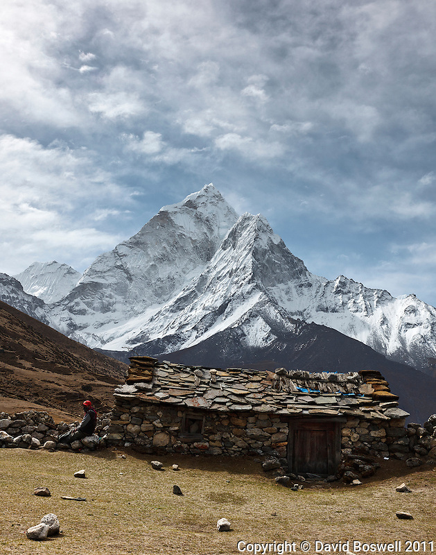 A sherpa rests near a stone house above the village of Dingboche in the Khumbu Valley, Nepal with Ama Dablam (22,493 ft/6856 m)in the background.