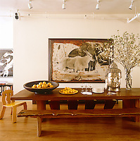 "A large head of Buddha sits on the dining tableand on the wall behind is ""Ele and Eland"" by Peter Beard"