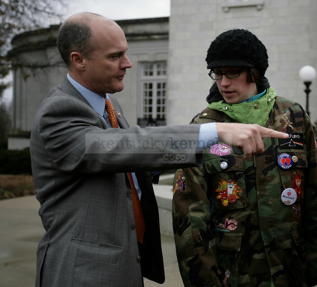 """Kentucky state trooper Greg Larimore tells a protester to stay off the garden mulch outside of the Governer's Mansion at I Love Mountains Day at the Kentucky State Capitol in Frankfort, Ky., on Tuesday, Feb. 14, 2012. An onlooker, Justin Wedes says """"They're telling us not to tear up the earth."""" Photo by Tessa Lighty 