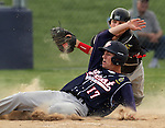 SIOUX FALLS, SD - JULY 1:  Justin Kautz #17 from Sioux Falls Post 15 West, slides into home as Jacob Mulder #12 from Valley Springs tries to put the tag on him in the fifth inning Monday night at Harmodon Park.  (Photo by Dave Eggen/Inertia)