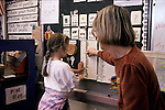 San Francisco CA 1st grade teacher giving student an achievement stick in class, rules for class conduct in background