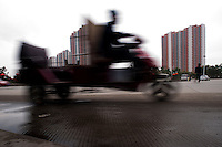 Daytime Landscape view of a man on a motorized tricycle driving in a Suburban Building Development in Xianyang, China.  © LAN