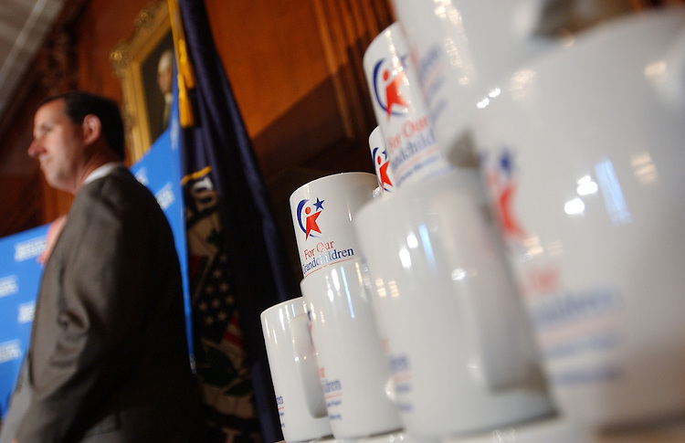 "Sen. Rick Santorum, R-Pa., stands near coffee mugs meant for awareness distribution at a ""For Our Grandchildren"" discussion with college students about the need for bipartisan cooperation to strengthen Social Security.."