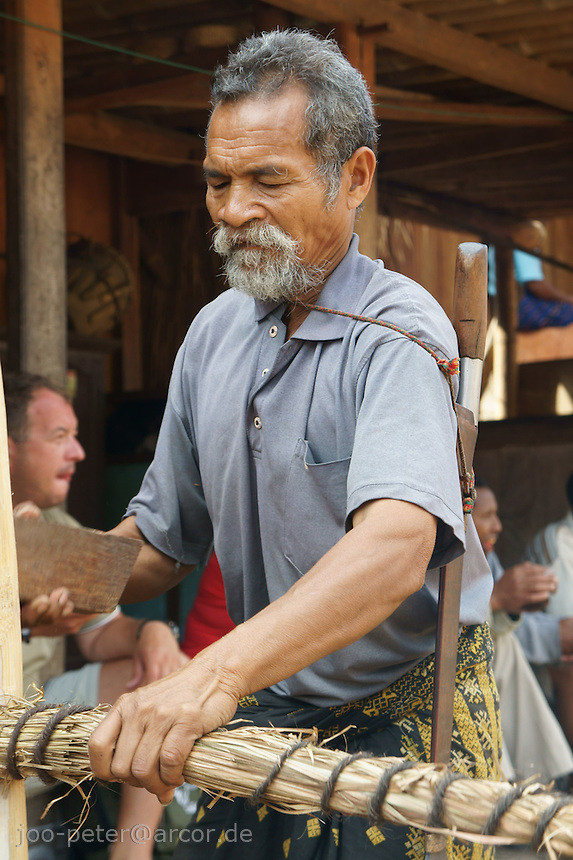 elder villager Franziskus proudly  helps in finishing the roof of a house as part of sacred celebrations of buidling a house, center of matriarchal society of Ngada people, village Bena near Bajawa,  Flores, Indonesia