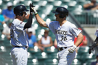 Kevan Smith (36) of the Charlotte Knights high fives teammate Patrick Leonard (20) after hitting a home run against the Gwinnett Stripers at BB&T BallPark on May 2, 2018 in Charlotte, North Carolina.  The Knights defeated the Stripers 6-5.  (Brian Westerholt/Four Seam Images)