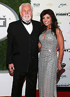 """20 March 2020 - Kenny Rogers, whose legendary music career spanned nearly six decades, has died at the age of 81. Rogers was inducted to the Country Music Hall of Fame in 2013."""" He had 24 No. 1 hits and through his career more than 50 million albums sold in the US alone. He was a six-time Country Music Awards winner and three-time Grammy Award winner. Some of his hits included """"Lady,"""" """"Lucille,"""" """"We've Got Tonight,"""" """"Islands In The Stream,"""" and """"Through the Years."""" His 1978 song """"The Gambler"""" inspired multiple TV movies, with Rogers as the main character. File Photo: 12 April 2014 - Phoenix, Arizona - Kenny Rogers, Wanda Miller. Muhammad Ali's Celebrity Fight Night XX held at the JW Marriott Desert Ridge Resort & Spa. Photo Credit: Miachelle DePiano/AdMedia"""