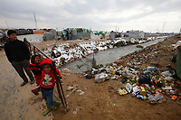 Syrian refugee children stand amongst snow, mud and rubbish, in an informal tented settlement in Lebanon's Bekaa valley, 30 January 2017.<br /> <br /> Picture: Russell Watkins/DFID