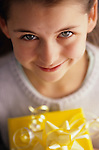 Colorful gift with yellow bow and yellow wrap celebrating a birthday with gift being held by a young girl (nine, 9 years old) smiling into camera.   MR