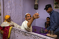 Rissani, Morocco.  Moroccan Offering Tea to the Photographer in the Market.