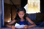 Juruena, Brazil. Young girl reading a letter in the window of her house with a hammock behind.