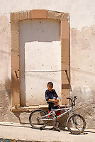 Mexican boy and bicycle in the 19th century mining town of Mineral de Pozos, Guanajuato, Mexico