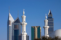 Dubai, United Arab Emirates. Emirates Towers and Dusit Thani Hotel with the dome and minarets of a mosque in the foreground. Sheikh Zayed Road, the Abu Dhabi Road, .