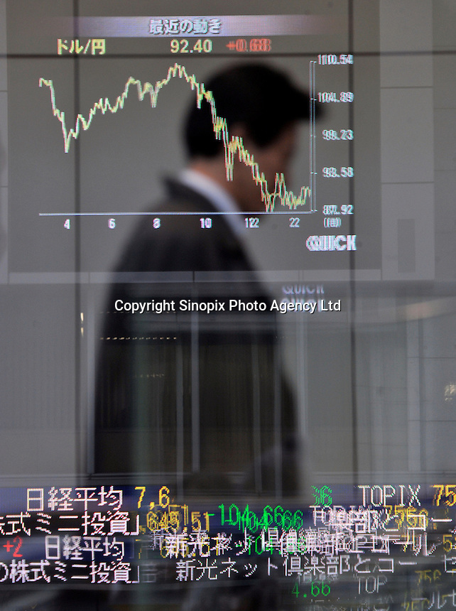 A businessman passes the reflection in a building of a stock exchange board in down-town Tokyo. Japan is suffering the biggest shrinking of its economy for 35 years. Shares in Tokyo slumped to their lowest in almost four months, as financial shares such as banks and property firms slid on continued credit worries...