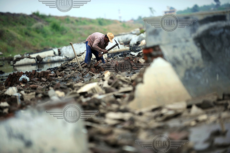55 year old Toyib scavenges for bricks, ceramic tiles and any items of value from his former home in the wreckage of Kedung Bendoh village. Since May 2006, more than 10,000 people in the Porong subdistrict of Sidoarjo have been displaced by hot mud flowing from a natural gas well that was being drilled by the oil company Lapindo Brantas. The torrent of mud - up to 125,000 cubic metres per day - continued to flow three years later.