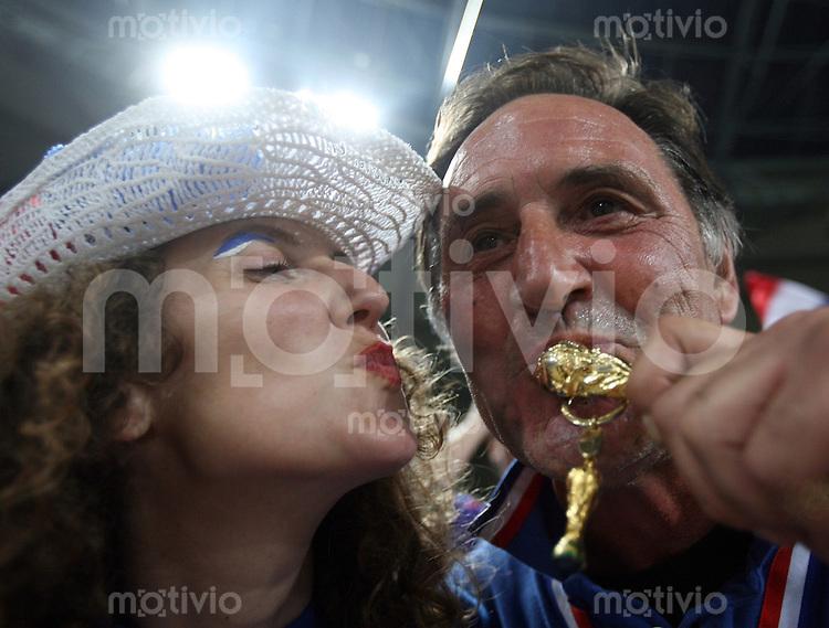 Fussball WM 2006  Achtelfinale   Spanien - Frankreich ; Spain - France  nach dem Spiel kuessen ein Mann und eine Frau eine Miniatur des Weltmeisterschaftspokal