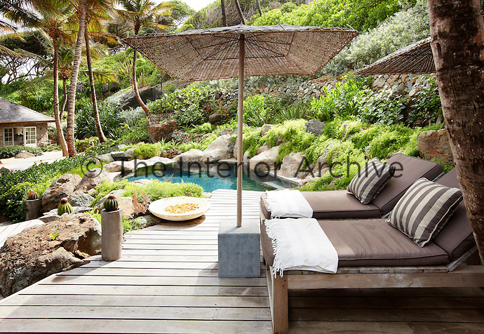 Two sun loungers and a parasol are arranged on a private decked area next to a plunge pool all set in a tropical garden.