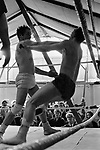 Tag wrestling in Pat McKeowen's fairground travellers boxing booth show, on The Hill, at the annual Derby horse race Epsom Down, Surrey, England 1969.<br /> Jack Turner (extreme left smoking)  he ran the fights at Pat McKeowen's  boxing booth. 1960s UK.