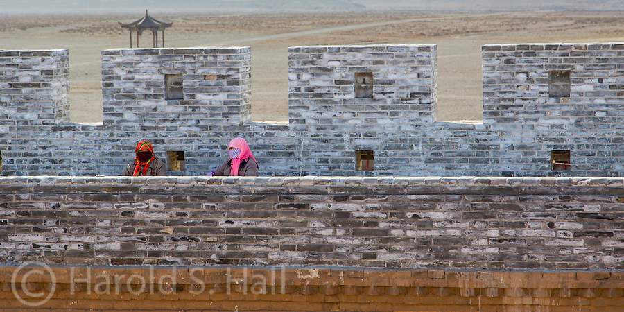 These Muslum women are sitting along an old milatary wall built around the Jiyuguan Fort near Dunhuang.