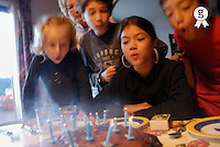 Family blowing candles out on birthday cake at home (blurred motion) (Licence this image exclusively with Getty: http://www.gettyimages.com/detail/73532494 )