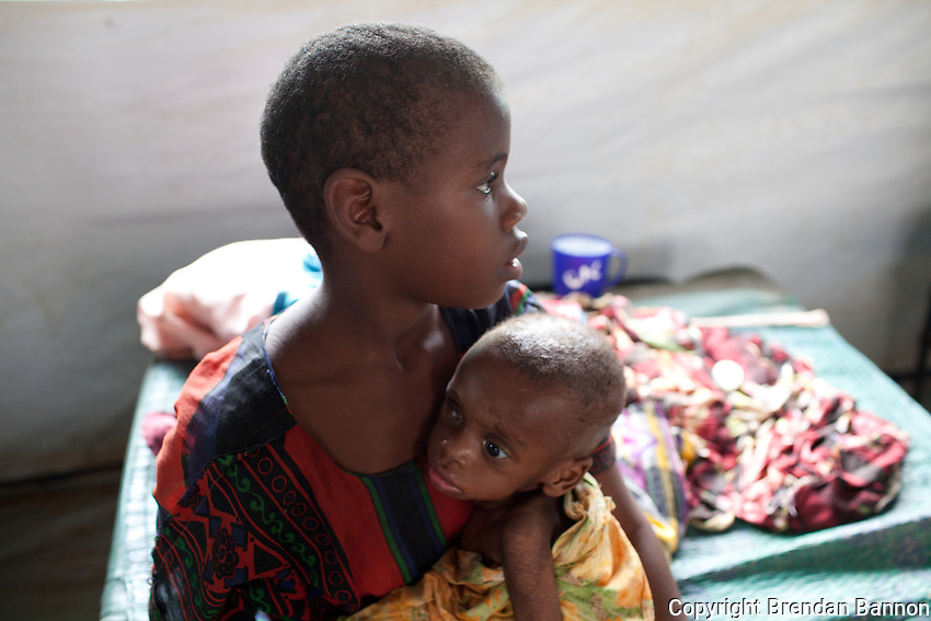 Gacalo Abdi Nunow holding her younger sister Matanay Abdi Nunow in the MSf hospital at Dadaab refugee camp in Northern kenya. The girls fled  from  their home near Mogadishu, somalia with their father Abdi Nunow. The youngest daughter is suffering from severe malnutrition.
