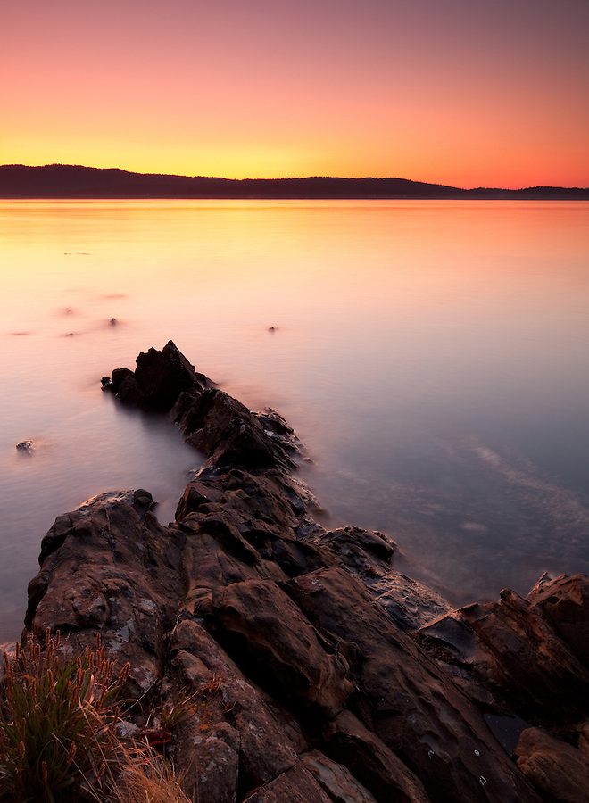 Sharp rocks are surrounded by the silky mist of waves washing up against them in this bright yellow and orange sunset seen from the shore of Portland Island.