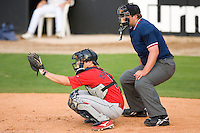 Catcher Travis D'Arnaud #5 of the Lakewood BlueClaws gives a target as home plate umpire Bryan Dormaier looks on at Fieldcrest Cannon Stadium May 16, 2009 in Kannapolis, North Carolina. (Photo by Brian Westerholt / Four Seam Images)