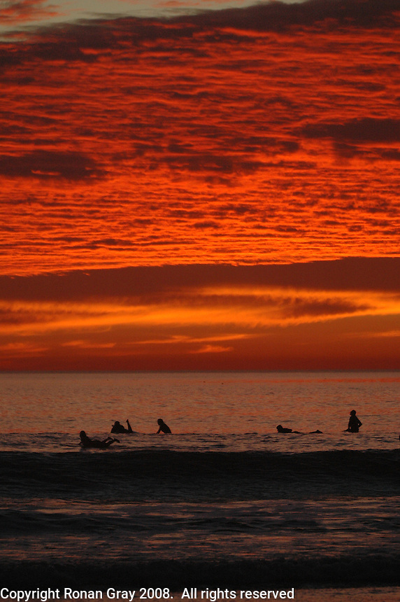 Pacific Beach, San Diego, California, USA:  Monday, January 19 2009.  A group of surfers are silhouetted against the sunset as they wait in the line up at the bottom of Loring Street.  The Martin Luther King Jnr Day holiday was marked by warm weather, big surf and a technicolored sunset as much of the rest of the country shivered in the cold.