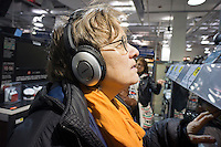 """A customer in a Best Buy store in New York listens on Bose headphones on Saturday, March 31, 2012. Best Buy recently announced that it will be closing 50 of its """"big box"""" stores and opening 100 smaller ones.  (© Richard B. Levine)"""