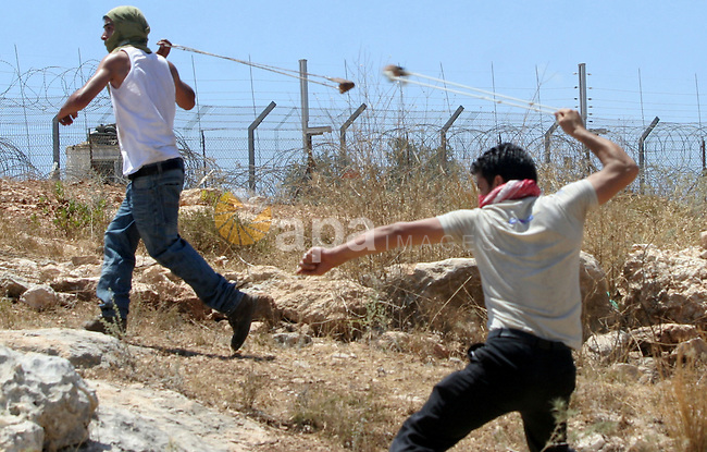 A Palestinian and foreign protesters clash with Israeli soldiers during a demonstration against Israel's controversial separation barrier in the West Bank village of Bilin near Ramallah on July3,2009. Photo by Nedal Shtieh