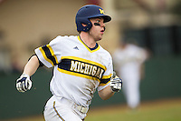 Michigan Wolverines shortstop Travis Maezes (9) runs to first base during the NCAA baseball game against the Washington Huskies on February 16, 2014 at Bobcat Ballpark in San Marcos, Texas. The game went eight innings, before travel curfew ended the contest in a 7-7 tie. (Andrew Woolley/Four Seam Images)