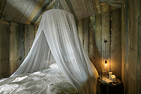 The sleeping cabin is filled with the softness of a filmy mosquito netting suspended from the recycled wooden ceiling