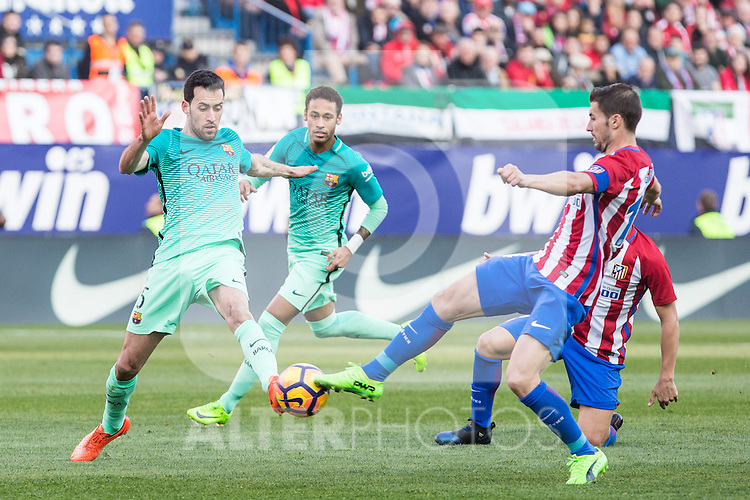 Sergio Busquets of Futbol Club Barcelona competes for the ball with Gabi Fernandez of Atletico de Madrid  during the match of Spanish La Liga between Atletico de Madrid and Futbol Club Barcelona at Vicente Calderon Stadium in Madrid, Spain. February 26, 2017. (ALTERPHOTOS)
