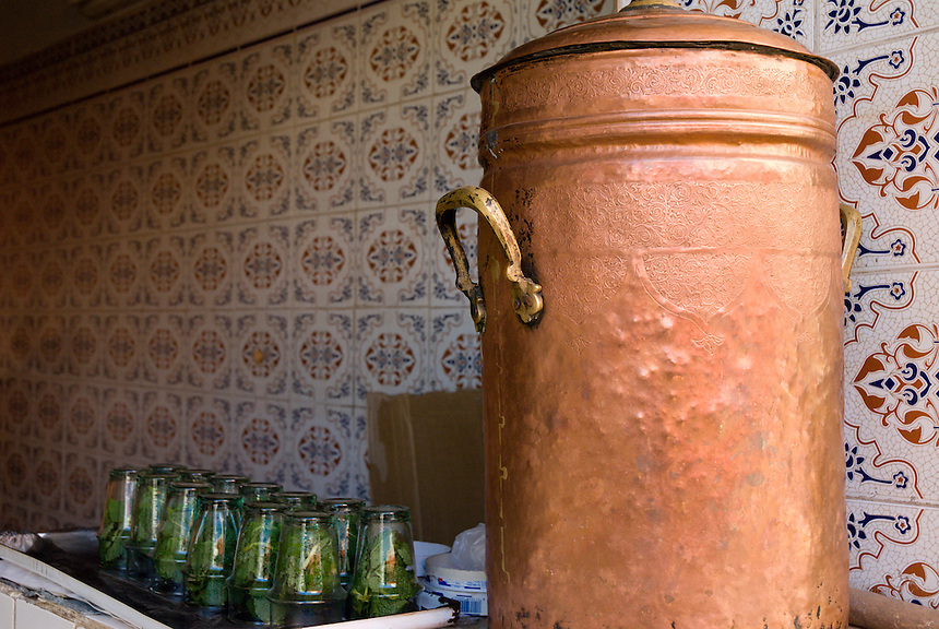 A copper water holder and cups full of fresh mint await customers for mint tea in a teashop in Fez, Morocco.