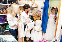 BNPS.co.uk (01202) 558833<br /> Picture: LauraJones/BNPS<br /> <br /> Eager customers Debbie Johnson, Denise Johnson and Stephanie Bossert wait patiently to try on a wedding dress whilst Amelia Platt trys one on in the only fitting room in the shop.<br /> <br /> A charity shop is being besieged by bargain-hunting brides after a mystery donor gave them 100 new wedding dresses.<br /> <br /> Staff at the PDSA store in Boscombe, Bournemouth, Dorset, were shocked when they opened several cardboard boxes left for them to find the pristine wedding and bridesmaid gowns inside.<br /> <br /> The garments have a combined retail price of more than &pound;50,000 but the charity shop is selling them for huge discounted prices. One gown worth &pound;1,500 is for sale for &pound;250.