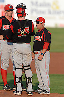 Batavia Muckdogs pitching coach Brendan Sagara (28) talks with catcher Chad Wallach (55) and pitcher Casey McCarthy (37) during a game against the Auburn Doubledays on August 28, 2013 at Falcon Park in Auburn, New York.  Auburn defeated Batavia 2-0.  (Mike Janes/Four Seam Images)