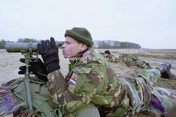 """Foto: VidiPhoto..EDE - Een verkenningspeloton van de Luchtmobiele Brigade in Schaarsbergen oefent op de Edese hei in het waarnemen van verstopte """"niet-natuurlijke"""" voorwerpen in het veld. Vrijwel dagelijks oefenen militairen in de bossen en op de hei bij Ede. (archieffoto)"""