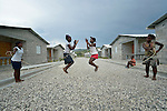 "Children jump rope in a model resettlement village constructed by the Lutheran World Federation in Gressier, Haiti. The settlement houses 150 families who were left homeless by the 2010 earthquake, and represents an intentional effort to ""build back better,"" creating a sustainable and democratic community."