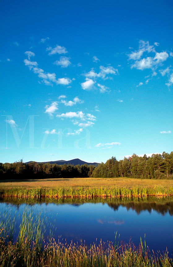 Scenic landscape with water in foreground and mountains in background. New Hampshire.