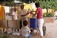 Woman buying ice cream from a street vendor in San Miguel de Allende, Mexico