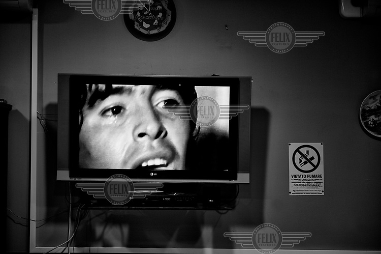 A restaurant television plays old footage of football player Diego Armando Maradona. The Argentine was a player for Naples for seven years from 1984 during which time the team enjoyed their most successful era. He left in disgrace after failing a drugs test but is stil revered as a hero in the city.