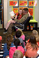 NWA Democrat-Gazette/BEN GOFF @NWABENGOFF<br /> Myra Cooper, 7, sits with her father Staff Sgt. William Cooper of Bentonville Monday, May 8, 2017, as he reads to her first grade classroom at Apple Glen Elementary School in Bentonville. Each week a parent comes in as a 'Mystery Reader' for their child's classroom at the school, with students receiving clues as to who it will be throughout the week. This week Myra was surprised by her father, who has been away from his family for over a year on deployment to Kuwait with the U.S. Army 77th Combat Aviation Brigade. Staff Sgt. Cooper read to the class from 'Harold and the Purple Crayon' by Crockett Johnson before taking Myra and the rest of their family to spend the day a the nearby Scott Family Amazeum.