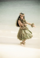 Woman dancing traditional hula in ti leaf skirt at beach