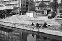 Workers on their lunch break near the sand hoppers at Naviglio dock, Milan, April 1970...Operai durante la pausa pranzo vicino alle tramogge della sabbia alla Darsena del Naviglio, Milano, aprile 1970.