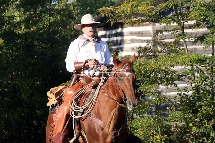 A cowboy riding his quarter horse near a old log cabin