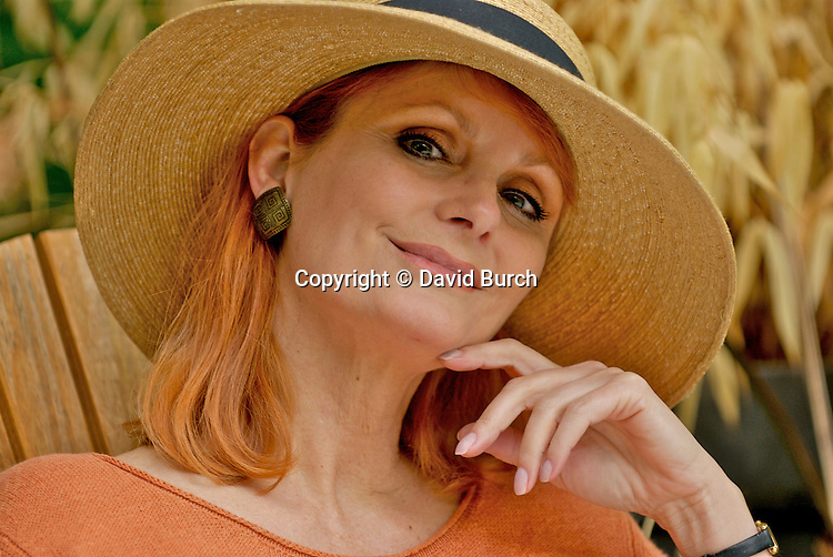 Mature woman wearing hat, smiling, portrait