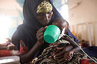 Kenya - Dadaab. A mother feeding her child suffering from severe malnutrition at the GTZ hospital.