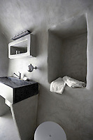 The sculpted walls of this simple hotel bathroom have been treated with tadelakt and coloured an anthracite grey